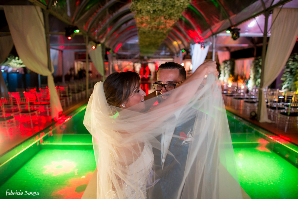 noiva brinca colocando o véu sob seu amado noivo