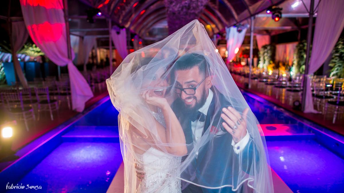 retrato do casal recem-casado feliz após cerimônia embaixo do véu da noiva