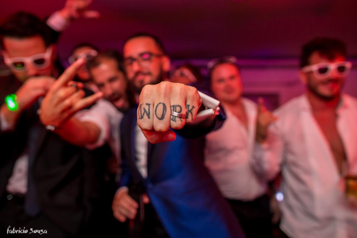 noivo Giu mostra sua mão com tatuagem Work e aliança de casamento