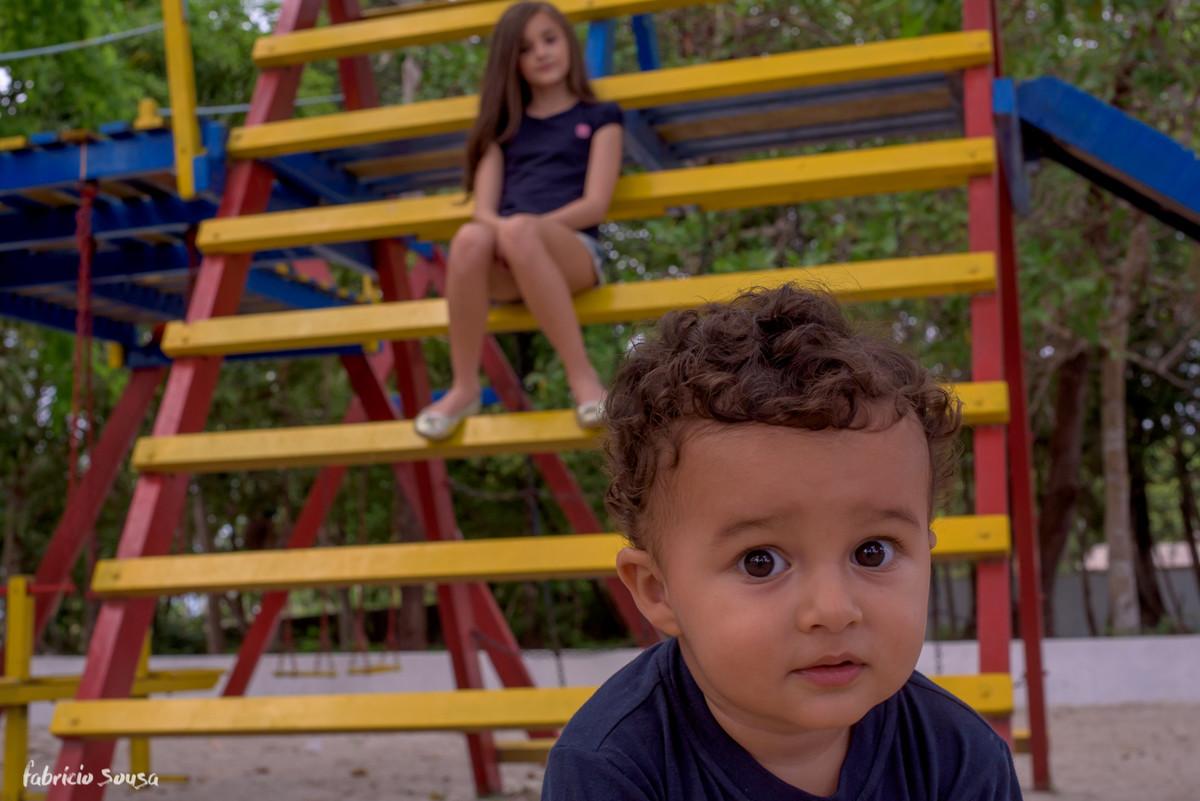 bebe olha diretamenta para câmera com sua irmã ao fundo