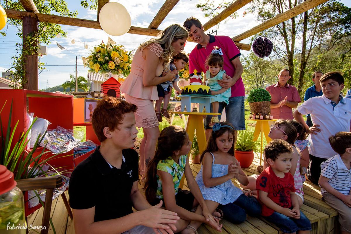 família assoprando as velinhas e crianças sentadas ao pé do bolo de aniversário infantil