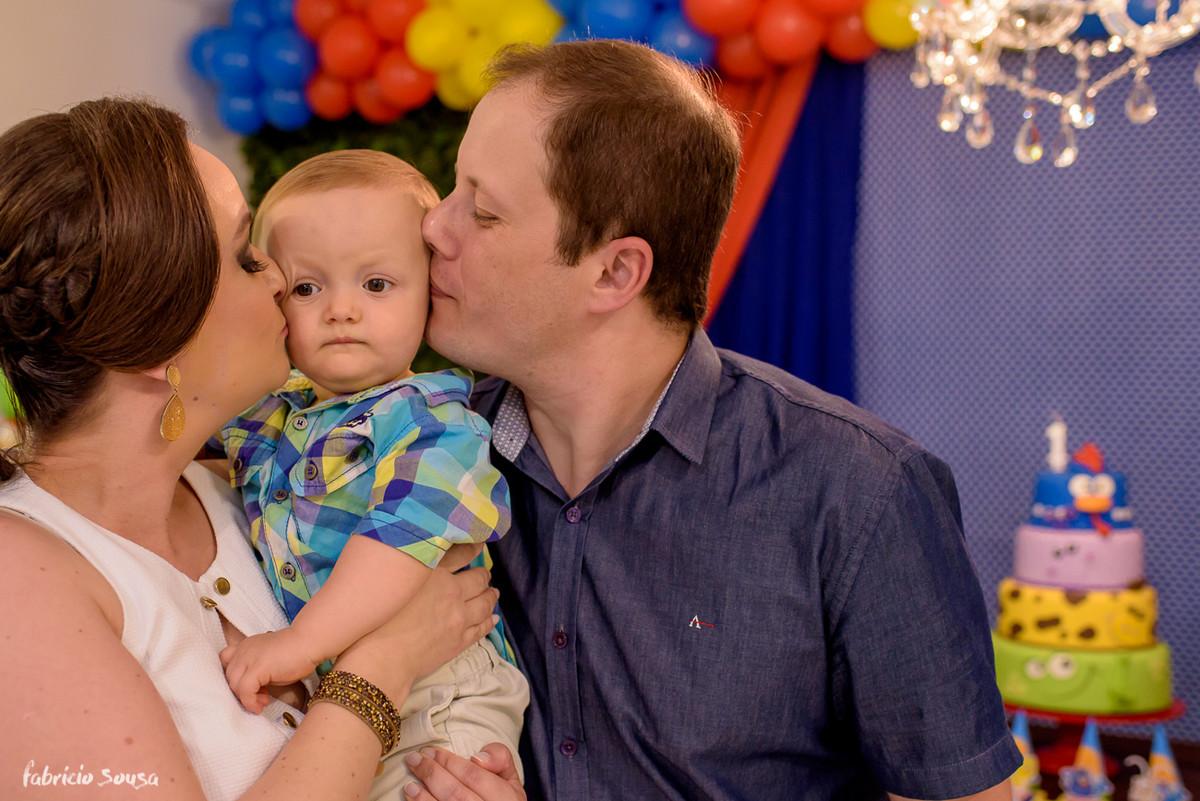 beijo duplo no aniversariante em frente ao bolo