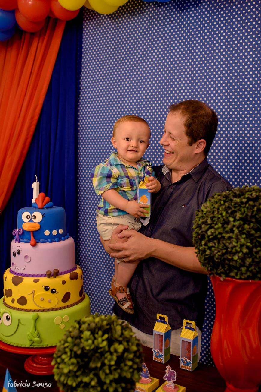 Gustavo Lima com seu filho Henrique atrás do bolo galinha pintadinha