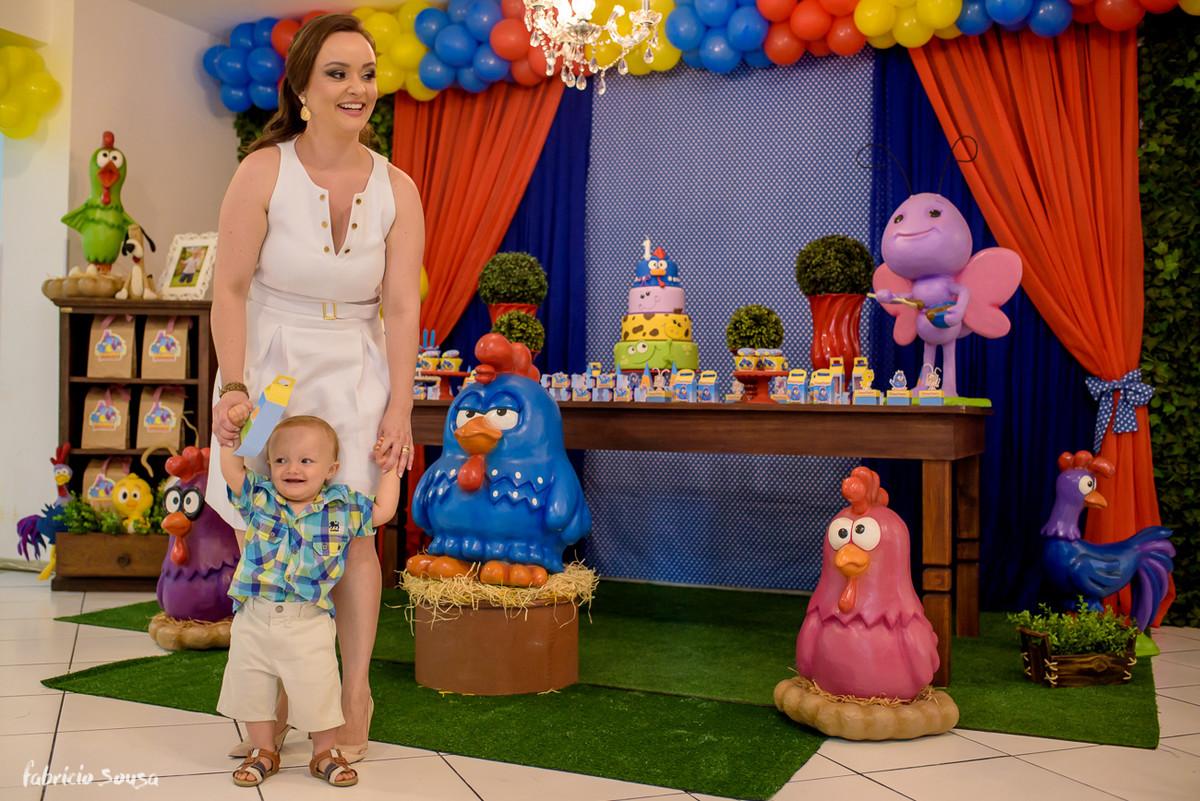 Mamãe com bebê sorridente em frente a sua decoracao de galinha pintadinha no primeiro aniversario