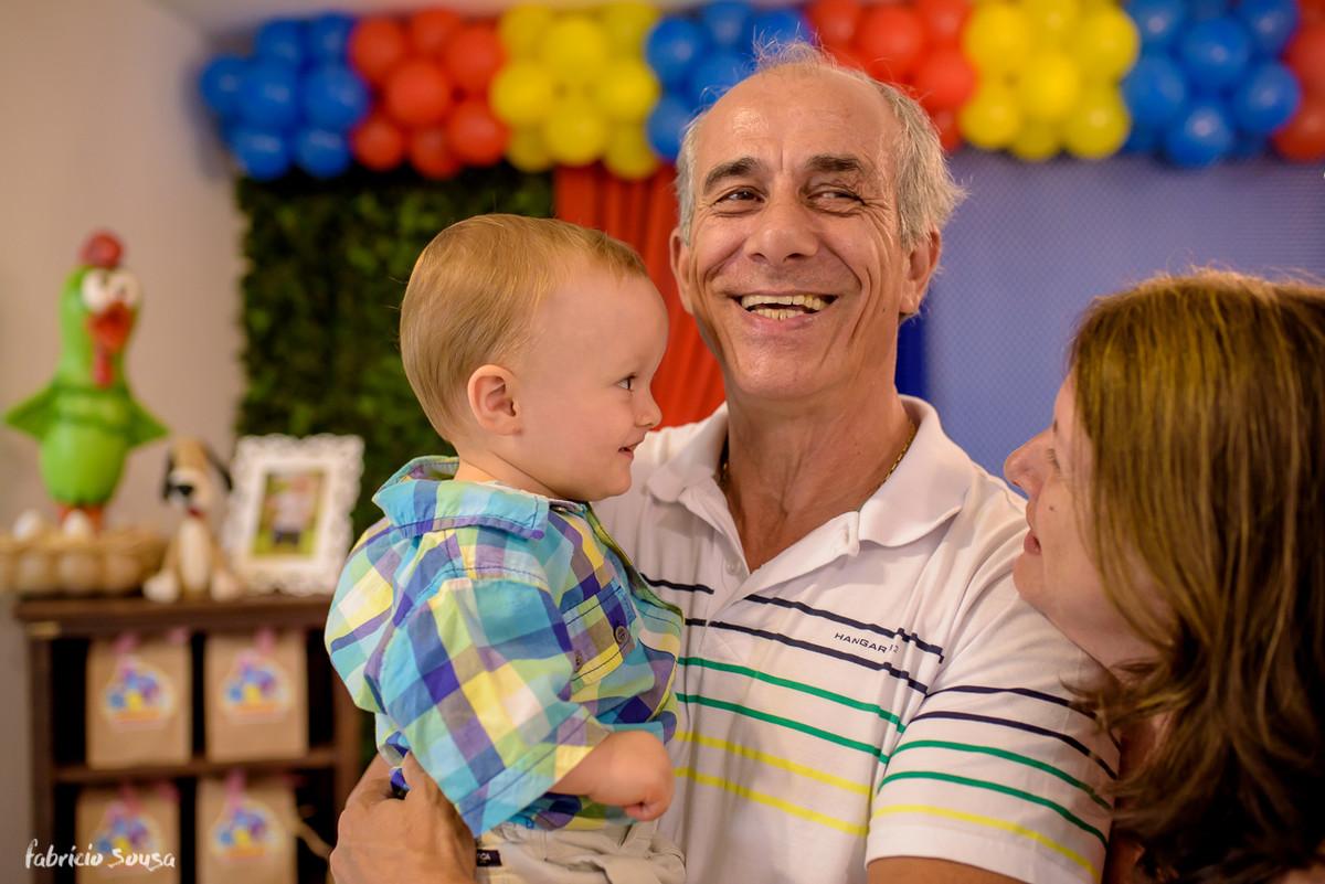 vovô todo orgulhoso e sorridente carregando seu neto Henrique no aniversário