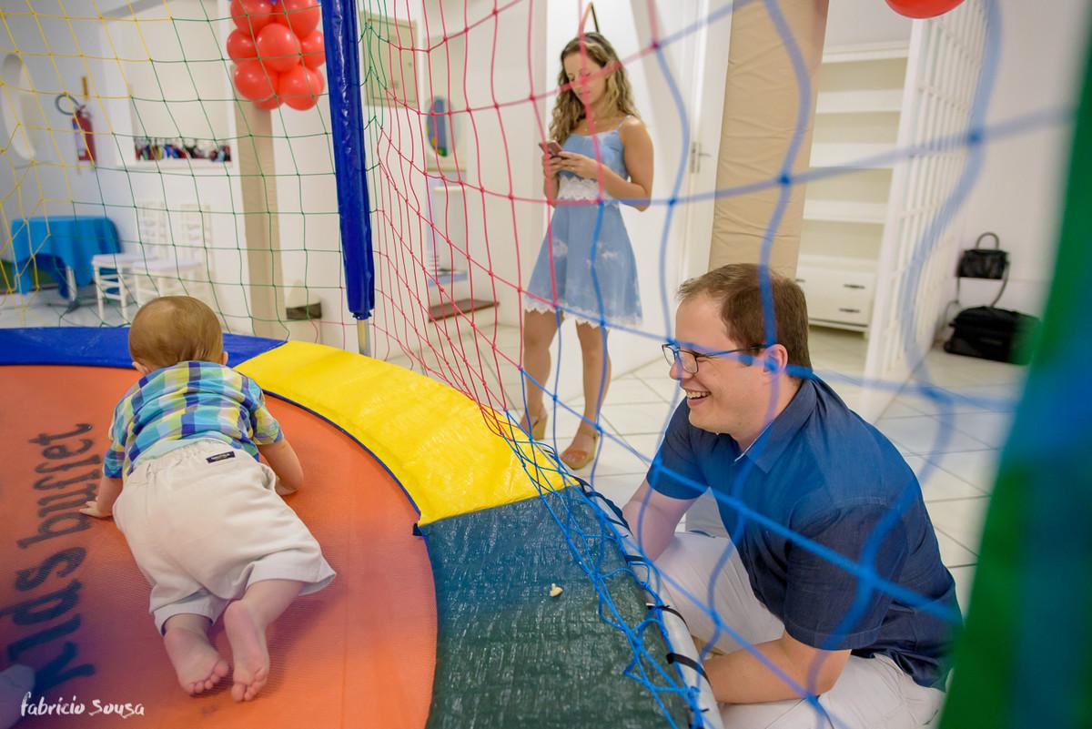 papai orgulhoso sorridente assiste filho brincando no pula-pula