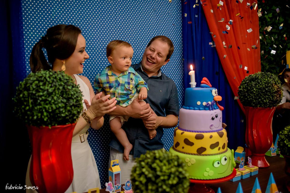 pais muito felizes cantando parabéns no primeiro aniversário infantil do filho