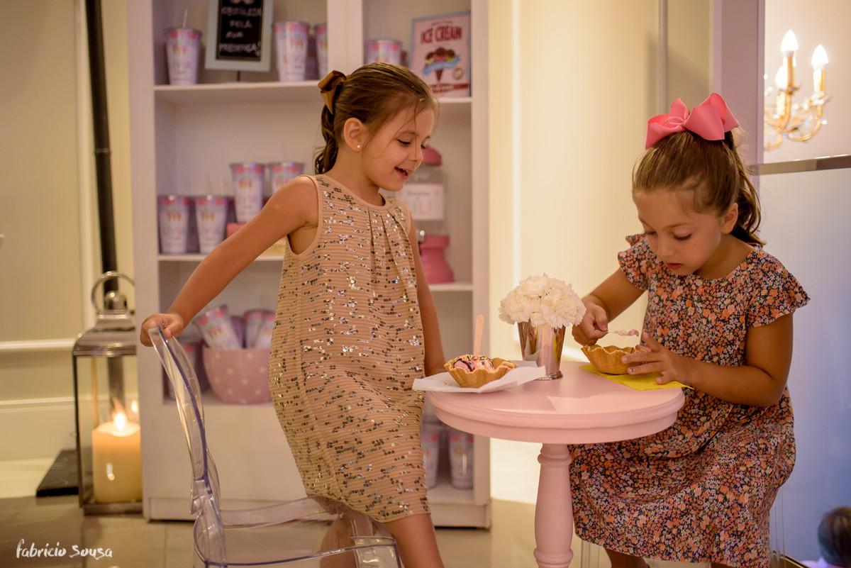 meninas sentadas tomando sorvete na mesa cor de rosa decorada por Thai Paisin
