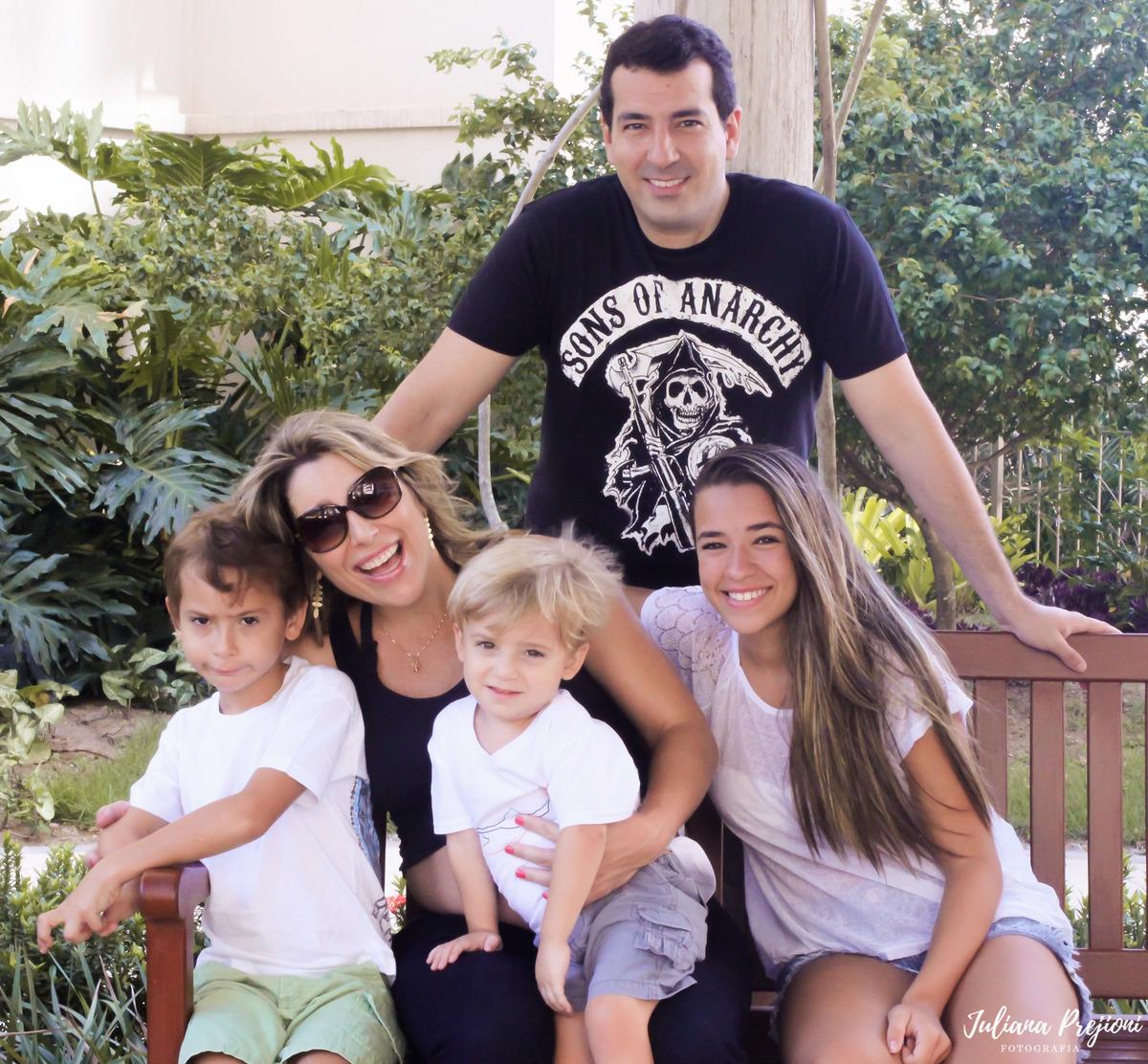 família sentada em um banco no jardim e sorrindo