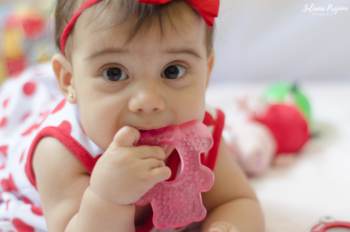 bebê brincando no chão com mordedor