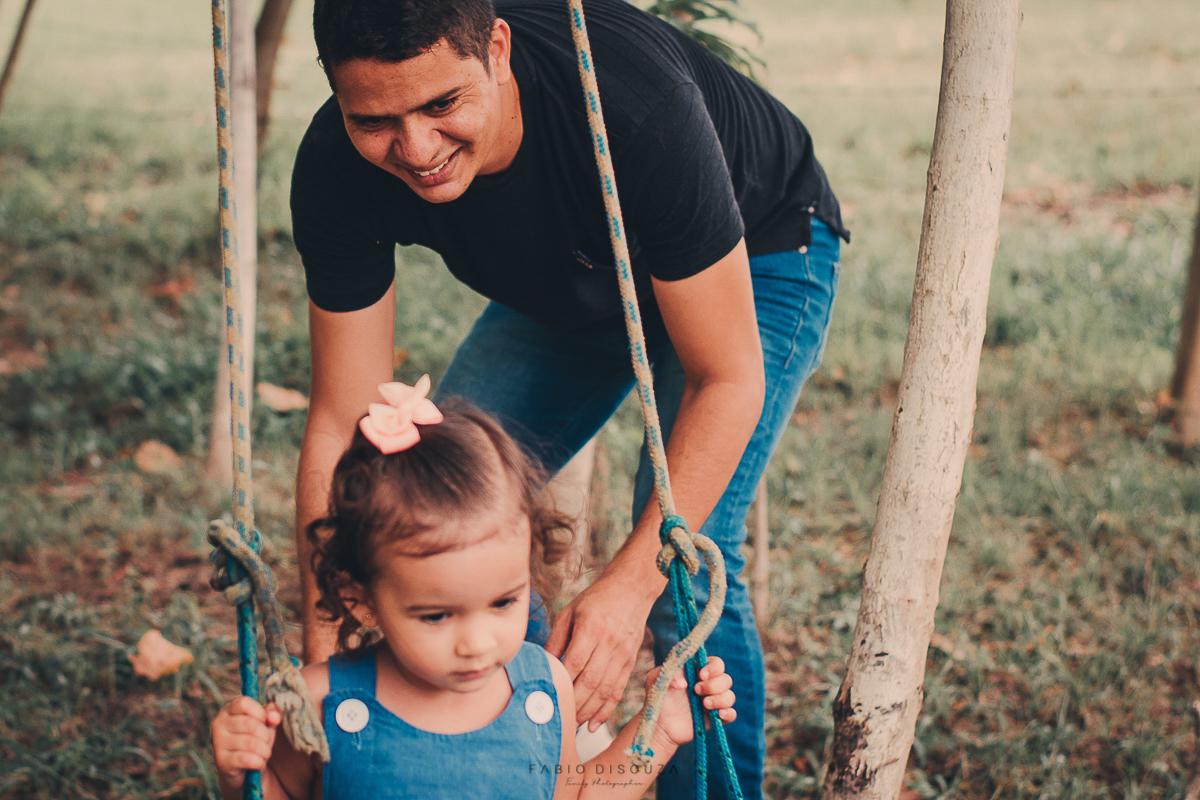 Ensaio de Família com pai e filha no balanço.