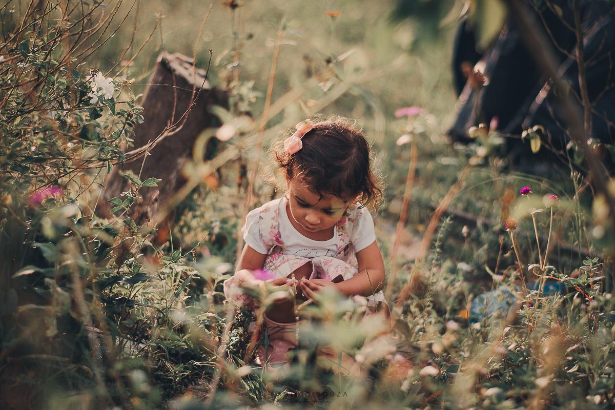 Criança brincando com flores. Pelo fotógrafo de Família, Fábio DiSouza, Dias Dávila-Ba.