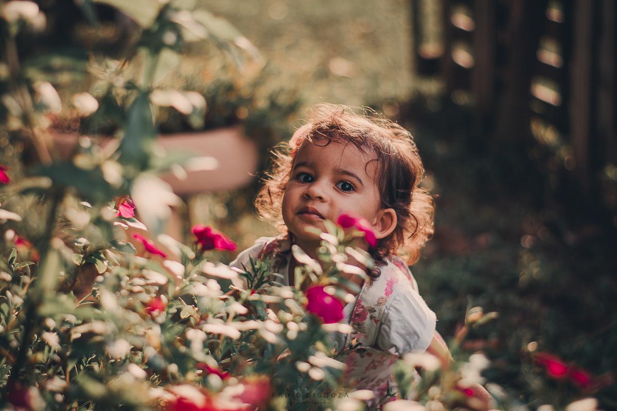 Criança brincando com flores. Pelo fotógrafo Fábio DiSouza,