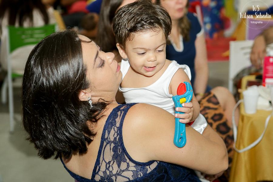 Nicholas com a mãe segurando um brinquedo azul
