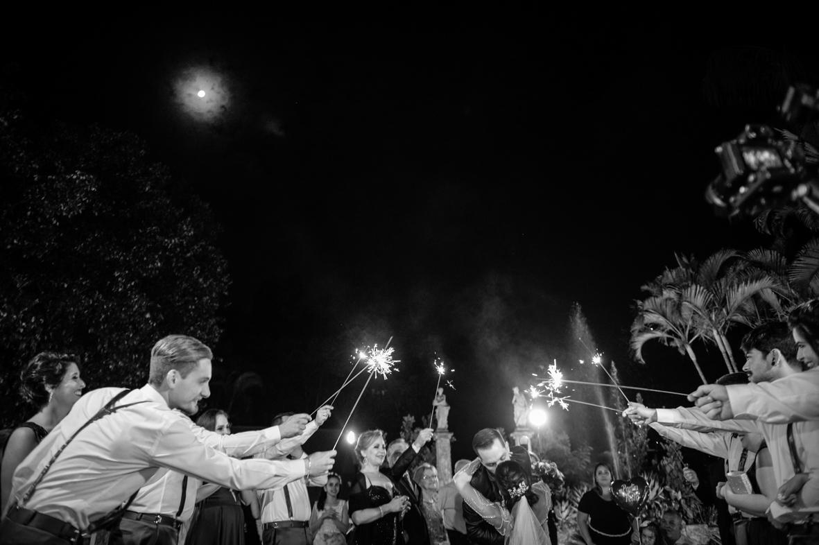 foto da saida da noiva mostrando todos os padrinhos segurando os sparkes e uma lua maravilhoso no ceu