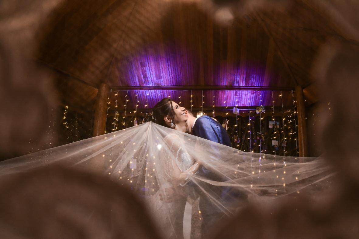 foto do vestido da noiva de costas mostrando o véu com o buque na mão e a calda toda aberta