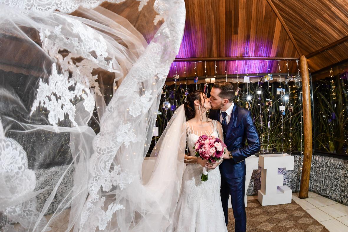 noiva e noivo se beijando com o véu voando