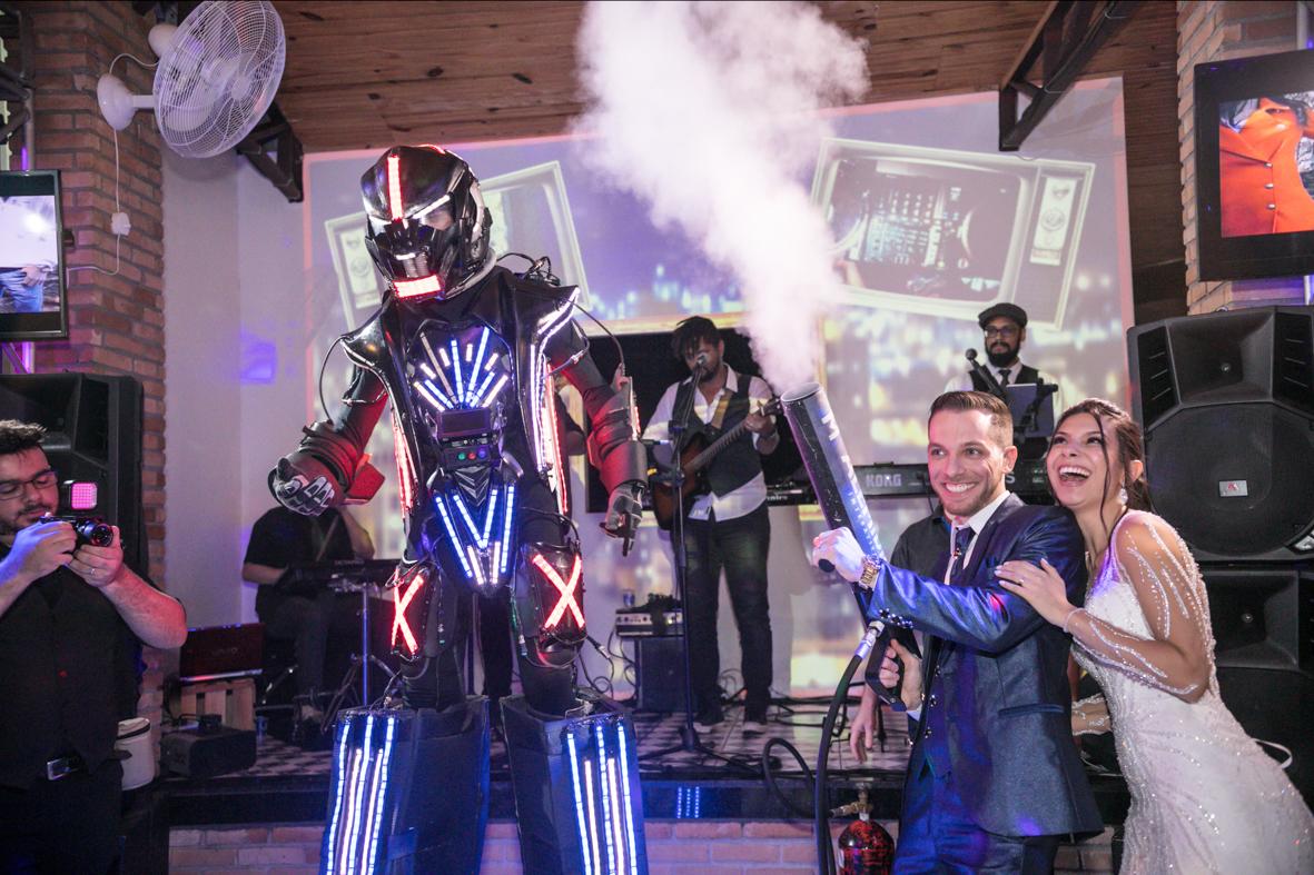 foto dos noivos junto com um robo de led soltando fumaca
