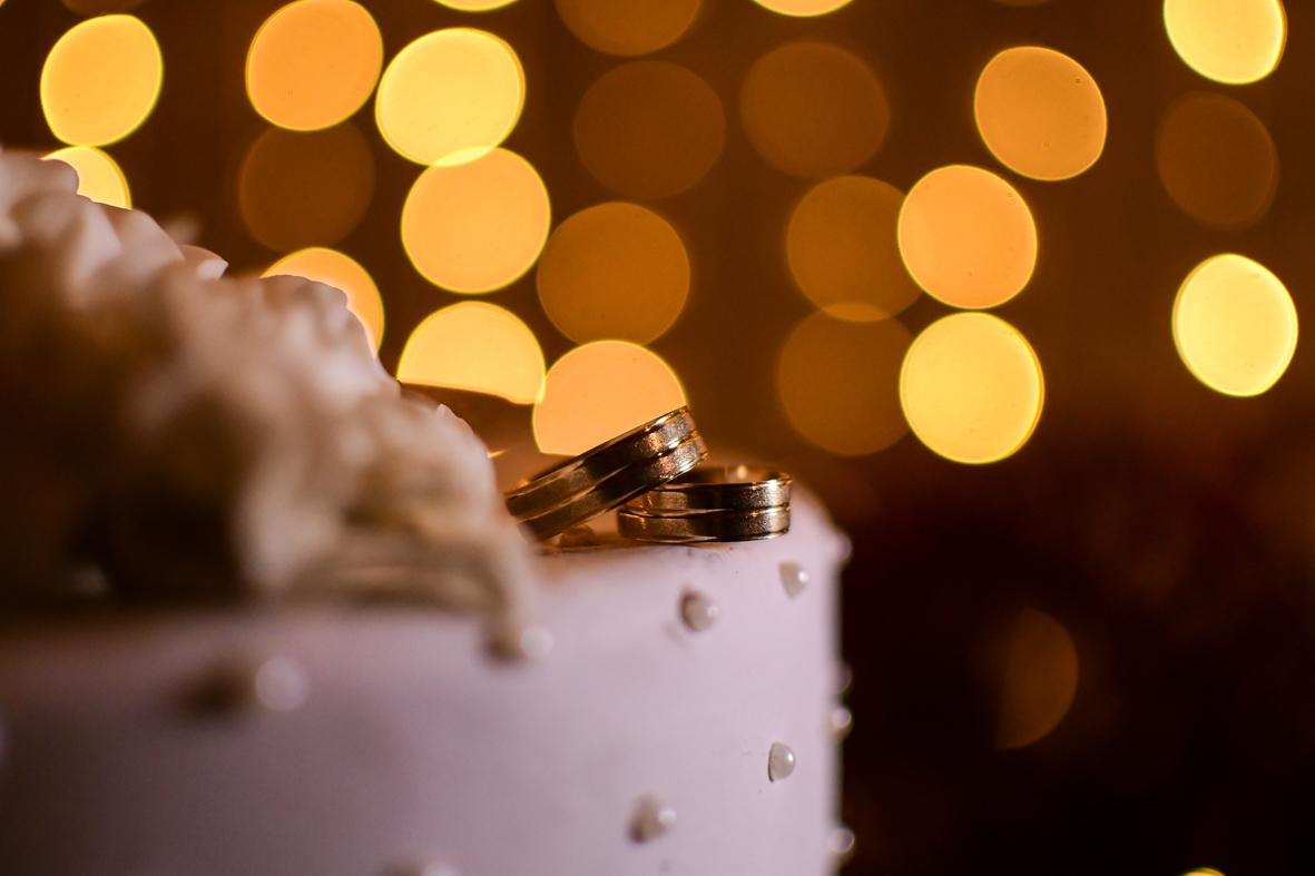 foto da aliança dos noivos com um fundo de luzes