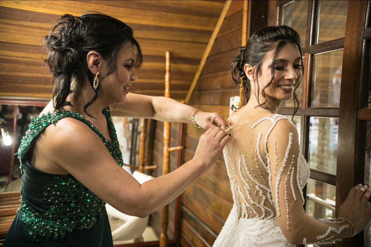 mae da noiva ajudando a noiva fechar o vestido