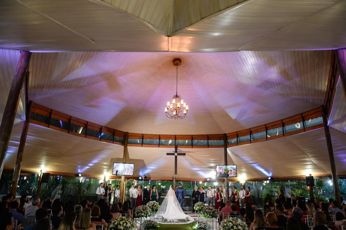foto tirada de tras mostrando o vestido o veu e toda cerimonia com sua decoração