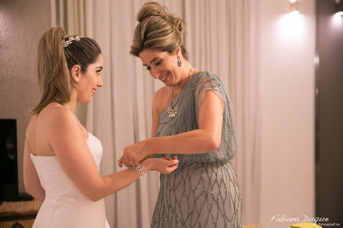 mão ajudando a noiva a se arrumar