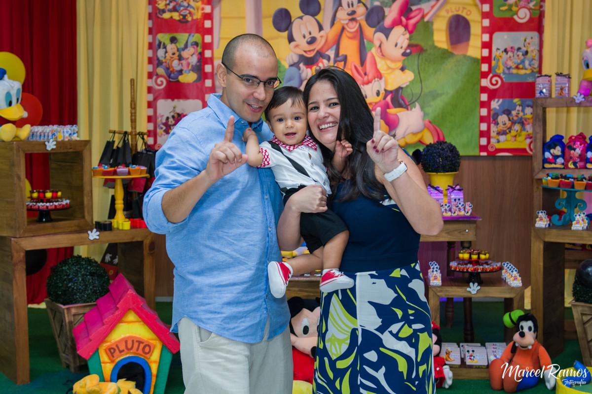 Papai, Mamãe e o aniversariante Gustavo sorrindo para o Fotógrafo de aniversário e festa infantil RJ | Marcel Ramos e atras deles a mesa decorada da turma do michey mouse