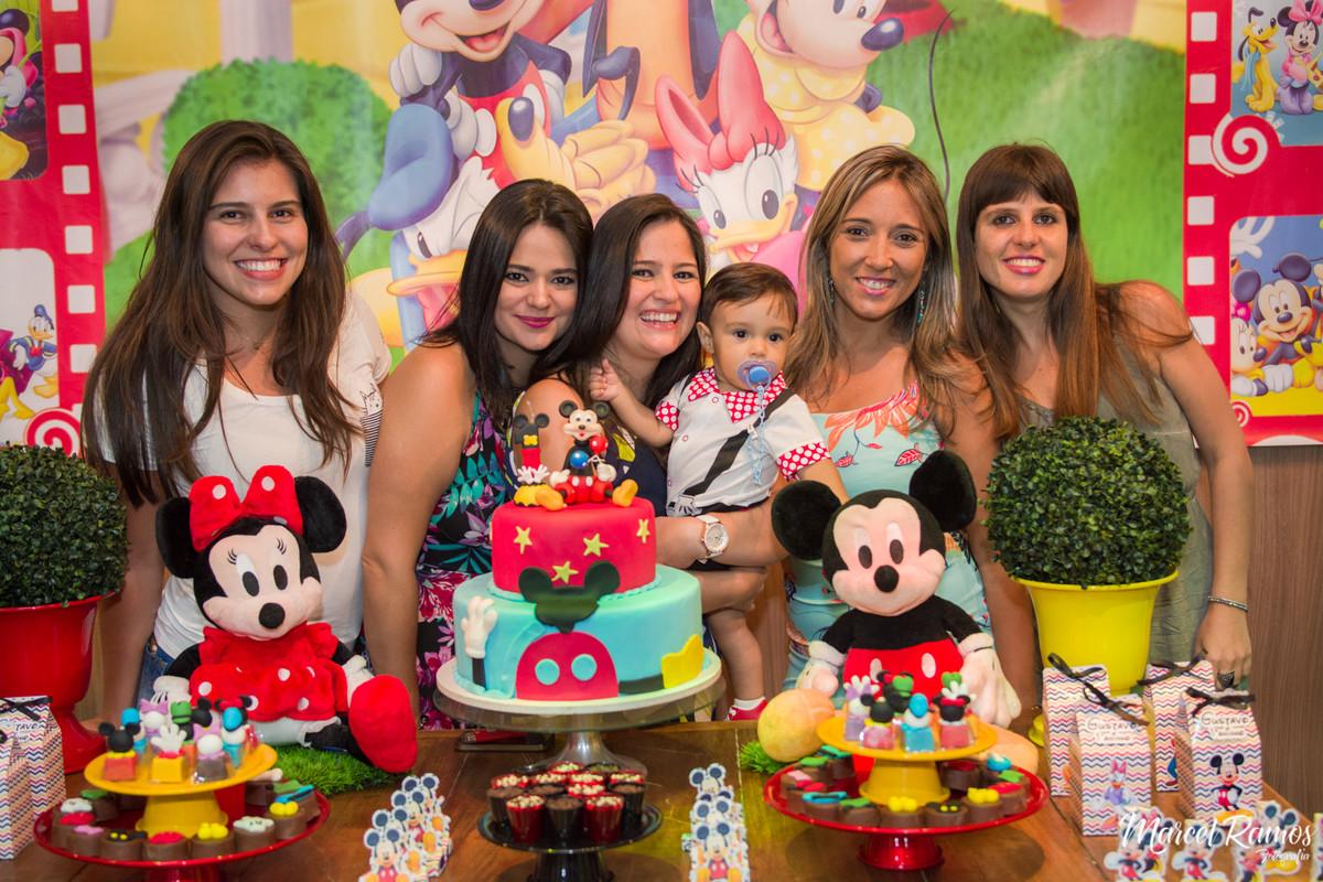 As meninas tirando foto na mesa do michey mouse com o aniversariante Gustavo