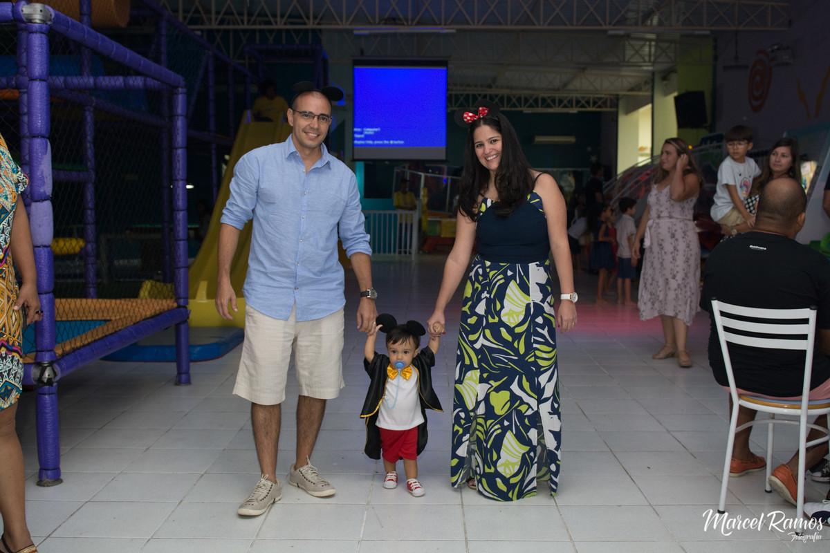 O aniversariante Gustavo caminhando com seus pais para a mesa do bolo vestindo a roupa do michey mouse.