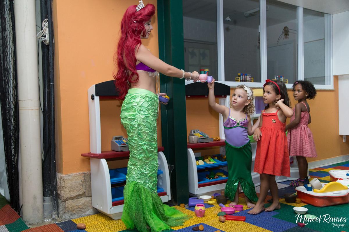 Personagem vivo da princesa Ariel brincando com as meninas de comidinha