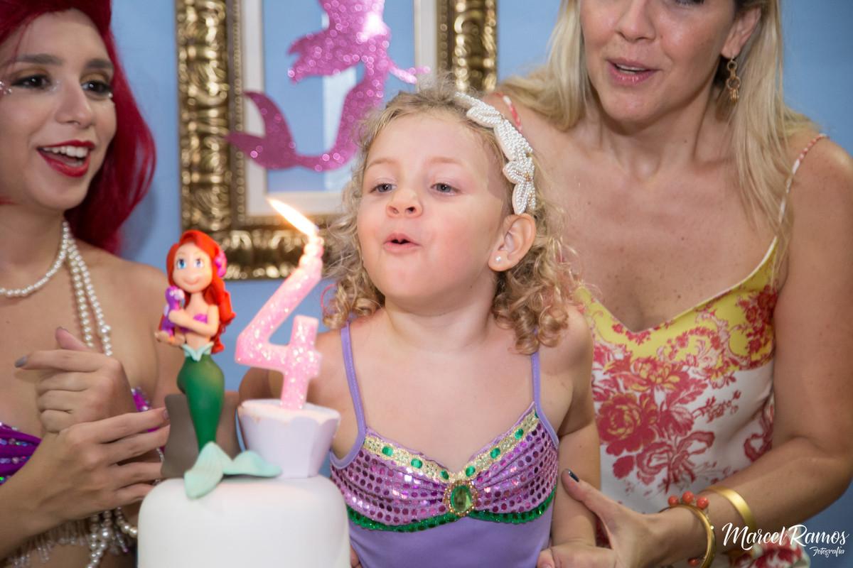 Isabela assoprando a vela da festa de seu aniversario no rj