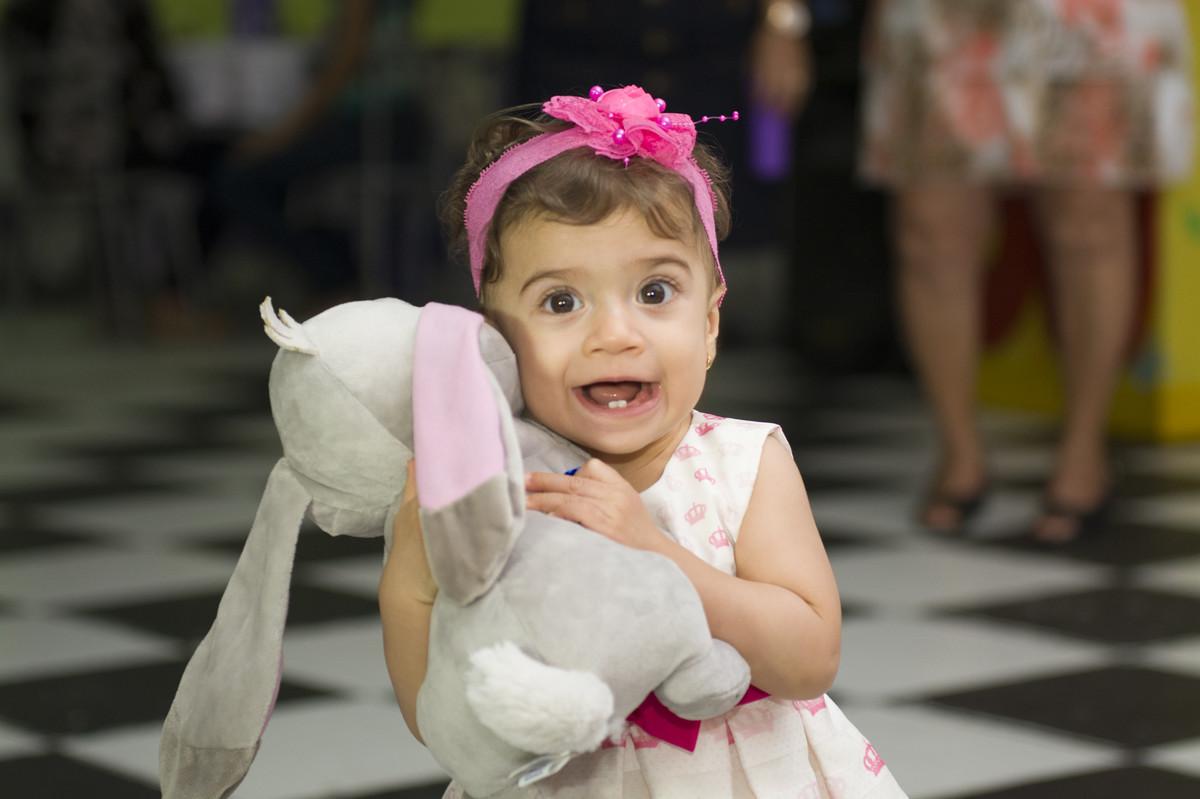 A aniversariante sofia pegou o bicho de pelucia da decoração de festa infantil para brincar a festa toda