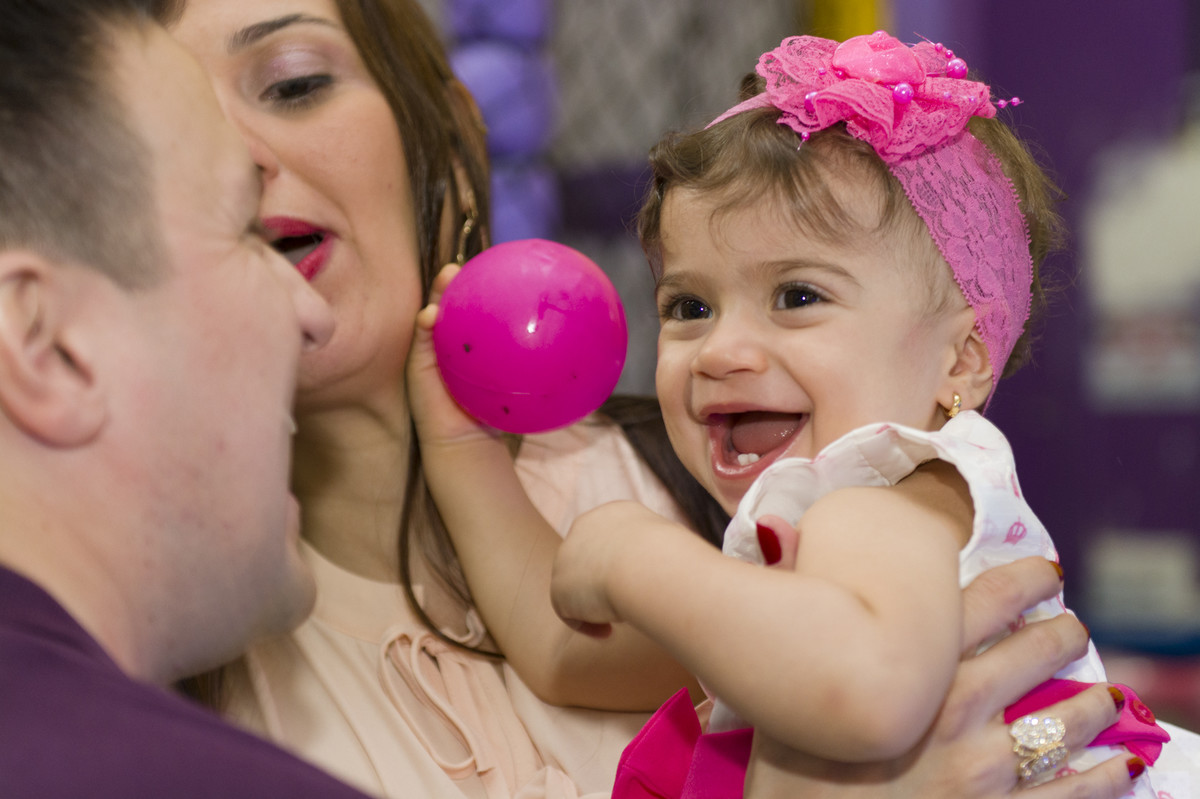 Sofia com uma bola rosa na mão mostrava o quanto estava feliz de completar um 1 ano de vida com sua família e seus amigos na casa de festa aquarius