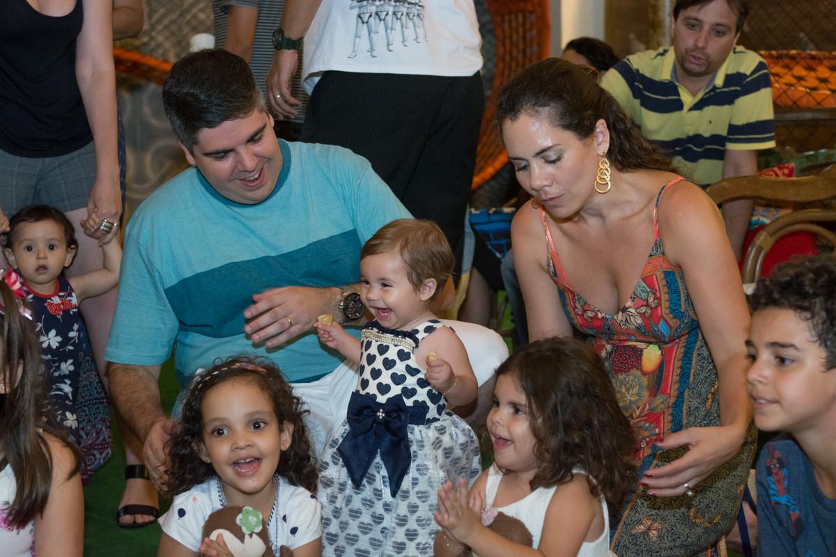 Mariana sorrindo junto com seus pais na hora da recreação em sua festa