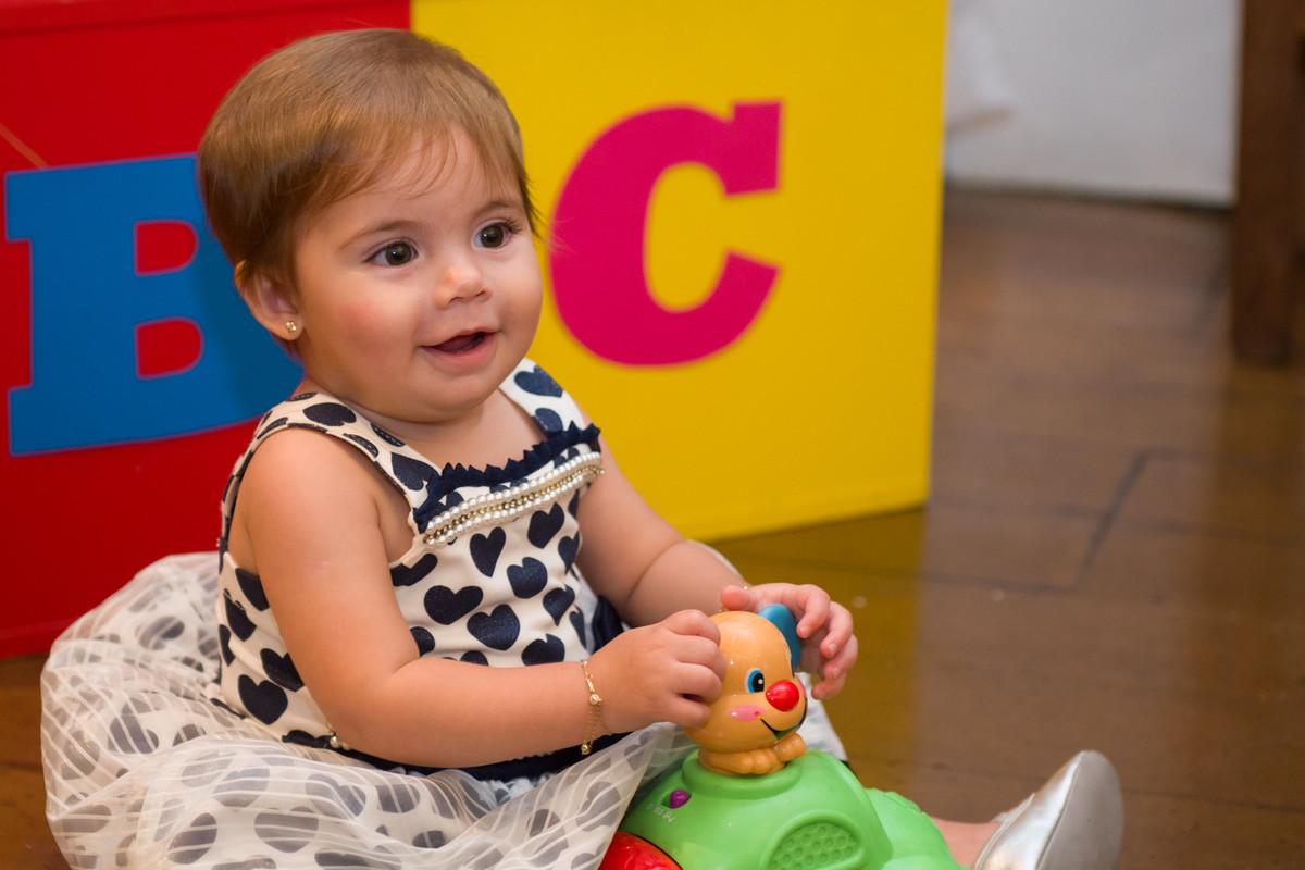 Mariana sentada no chão brincando e sorridente em sua festa de aniversário rj