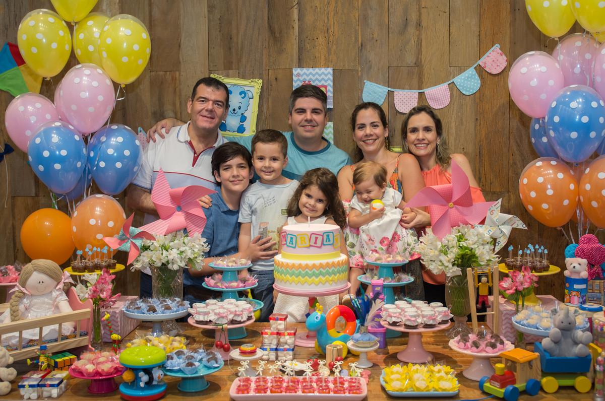 Família reunida para a fotografia de festa infantil na mesa decorada dos brinquedos