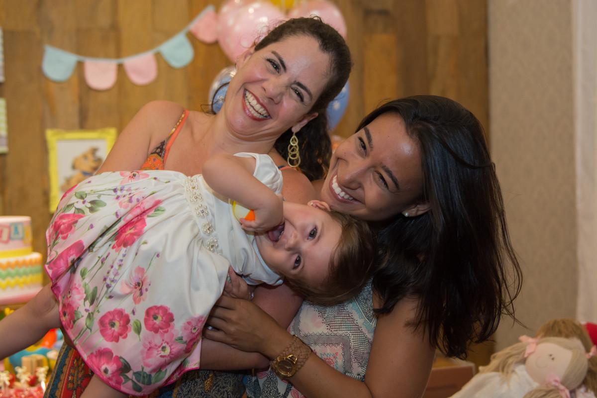 marcel ramos fotógrafo registro um sorriso da aniversariante mariana que estava no colo de sua mãe e ao lado de sua tia.