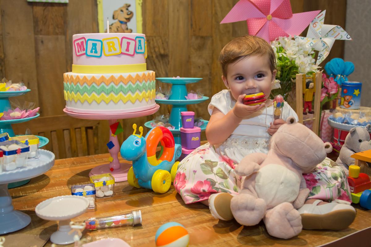 Mariana sentada na mesa decorada do seu aniversário com o ioiô na boca sendo fotografada pelo fotógrafo de aniversário e festa infantil RJ Marcel Ramos