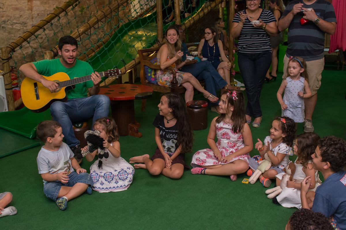Tio da recreação tocando violão para as criansas no aniversário da mariana no buffet quintal a noite
