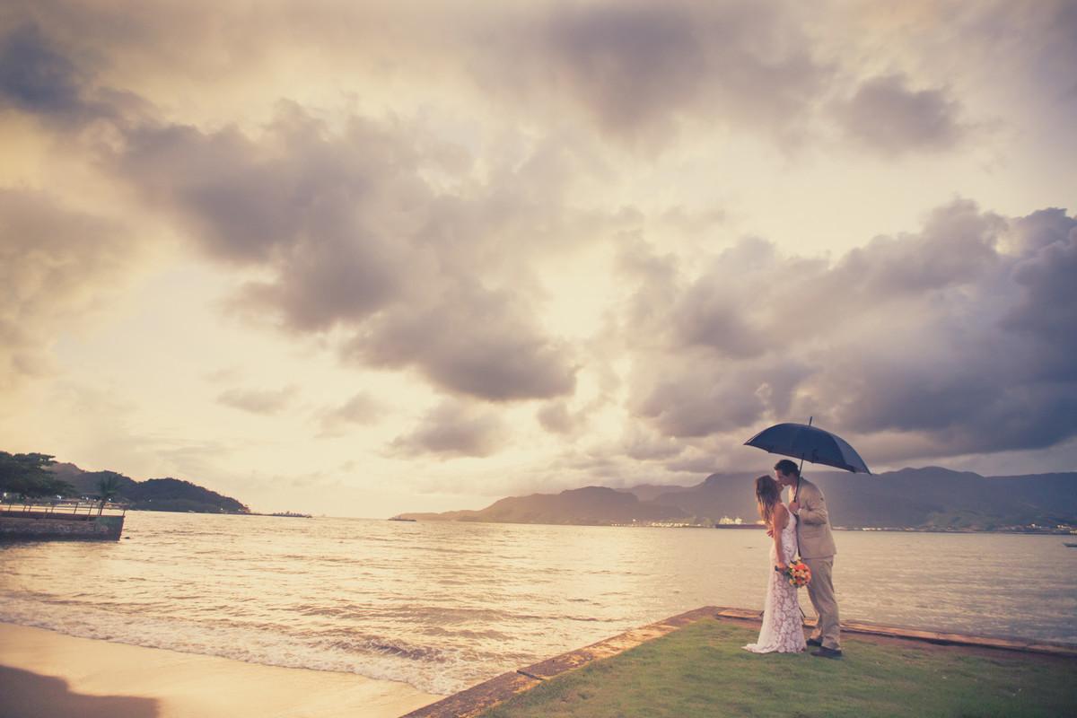 Noivos se beijando no por do sol na praia segurando um guarda-chuva