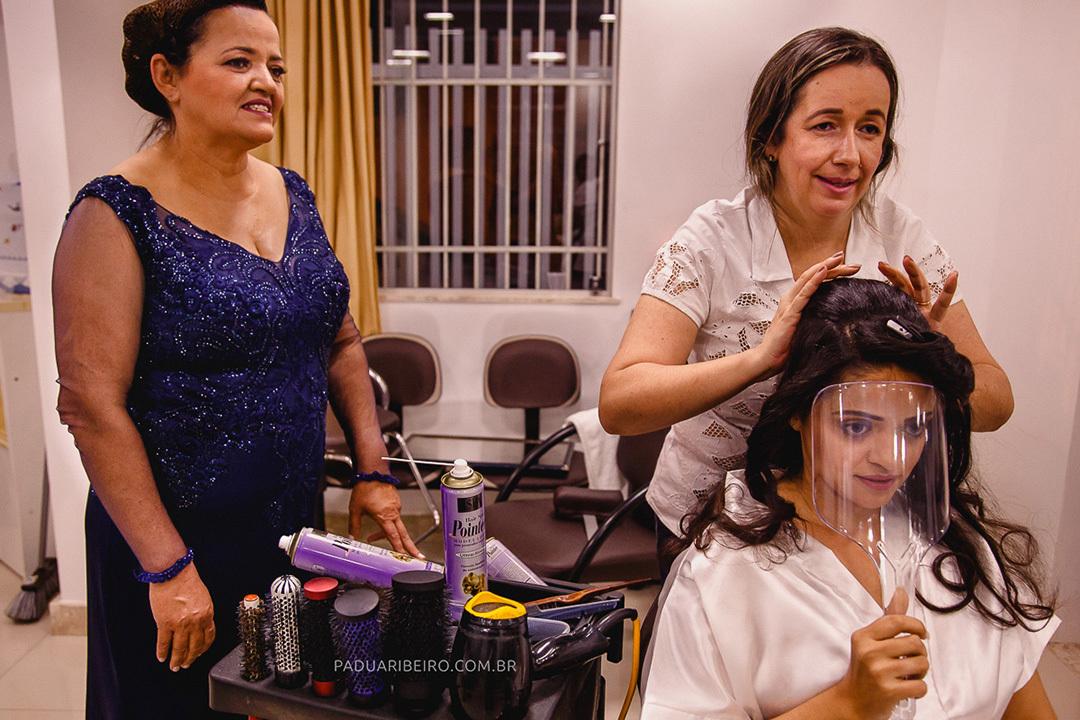 arrumando o cabelo da noiva e mãe ao lado