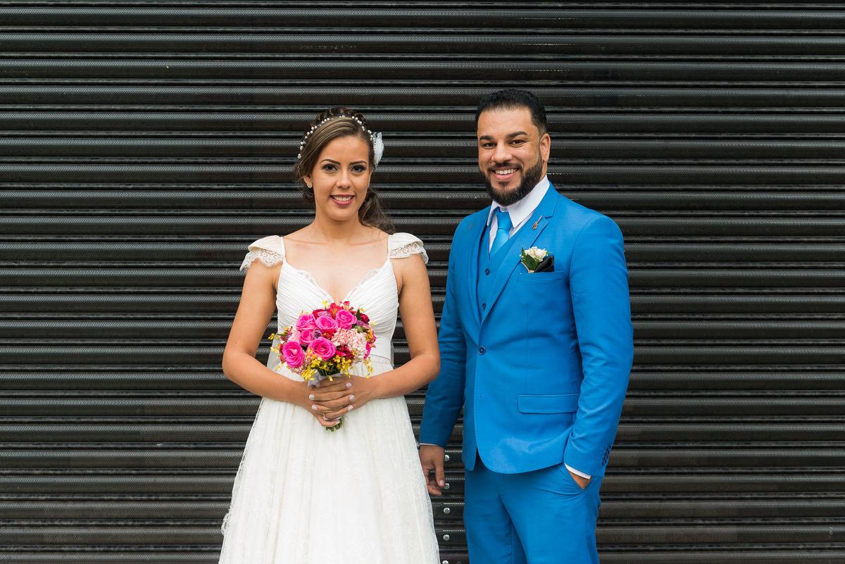 casal abraçados e noiva segurando o buquê colorido no Buffet Evento Perfeito  - fotografado por Max Nogueira