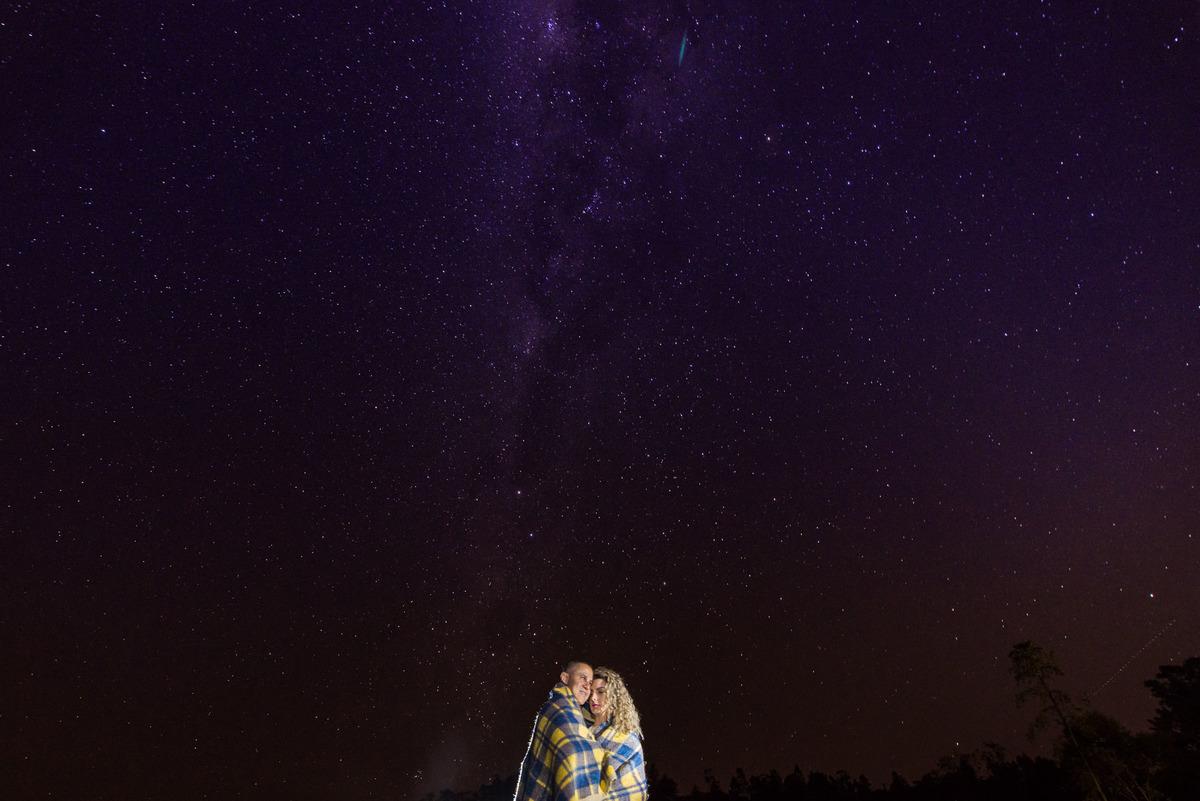 casal abraçados com o cobertor com um céu estrelado ao fundo no sitio São Francisco em Juquitiba  - fotografado por Max Nogueira