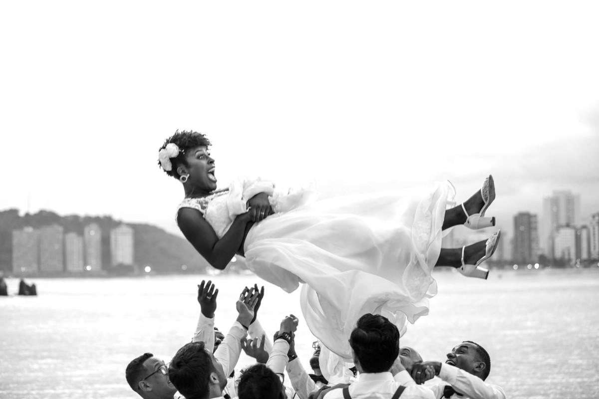noiva sendo jogada para o alto pelos seus padrinhos na praia de São Vicente - fotografado por Max Nogueira