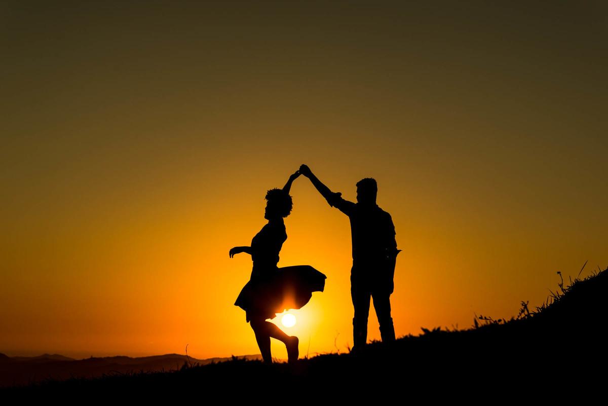 casal dançando ao nascer do sol no Pico do Olho D`Agua em Mairiporã casal abraçados e noiva segurando o buquê colorido no Buffet Evento Perfeito  - fotografado por Max Nogueira