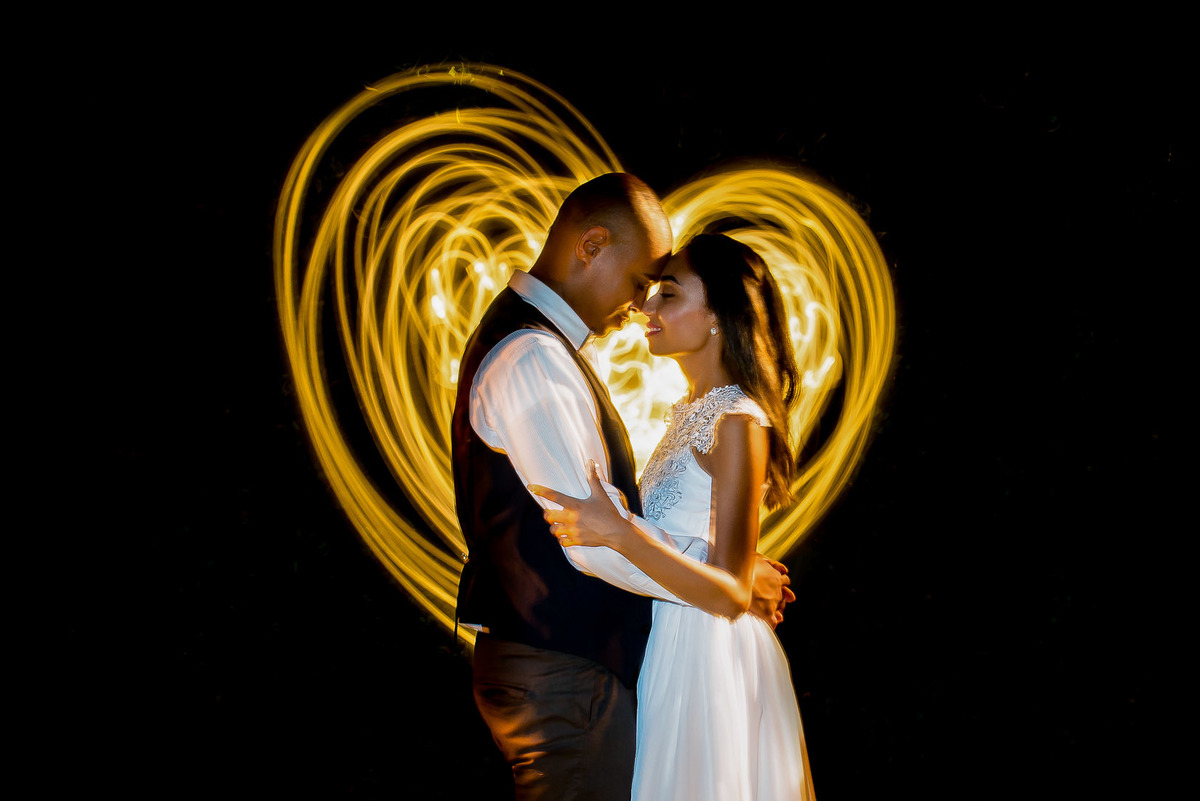 casal abraçados com coração iluminado ao fundo na cidade de Paraty no Rio de Janeiro - fotografado por Max Nogueira