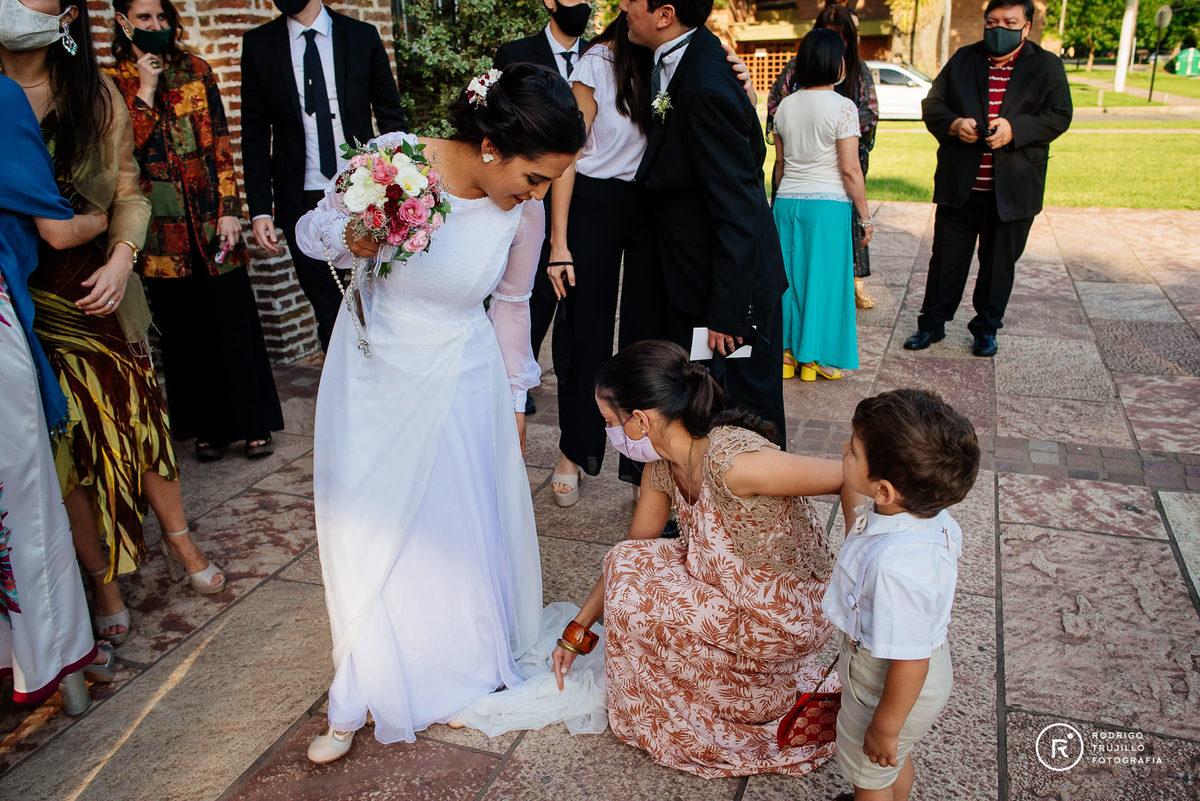 hermana de la novia acomodando el vestido a la salida de la iglesia con su sobrino, momentos de la boda, vestido bowdika bellisimo