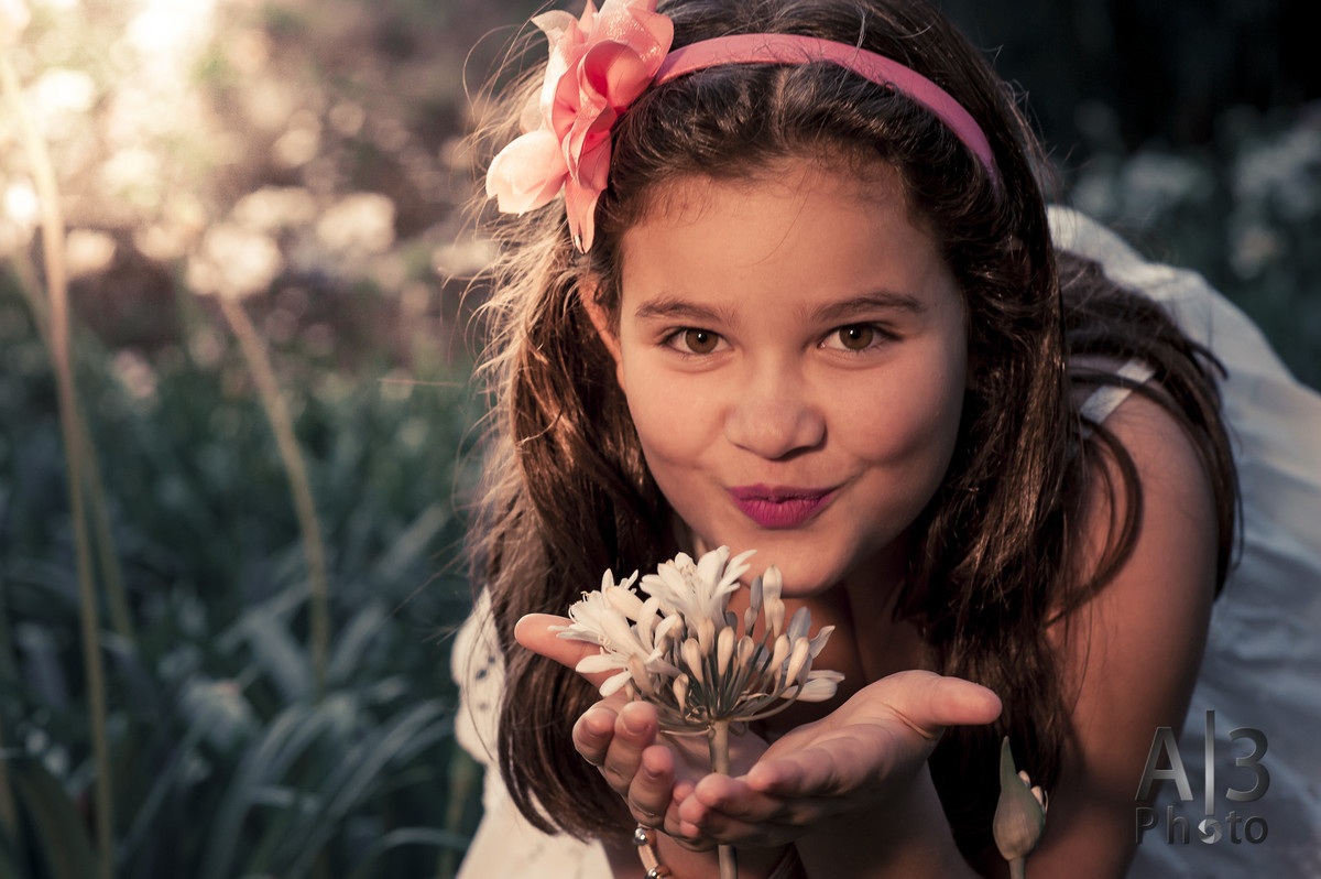 menina beijando uma flor