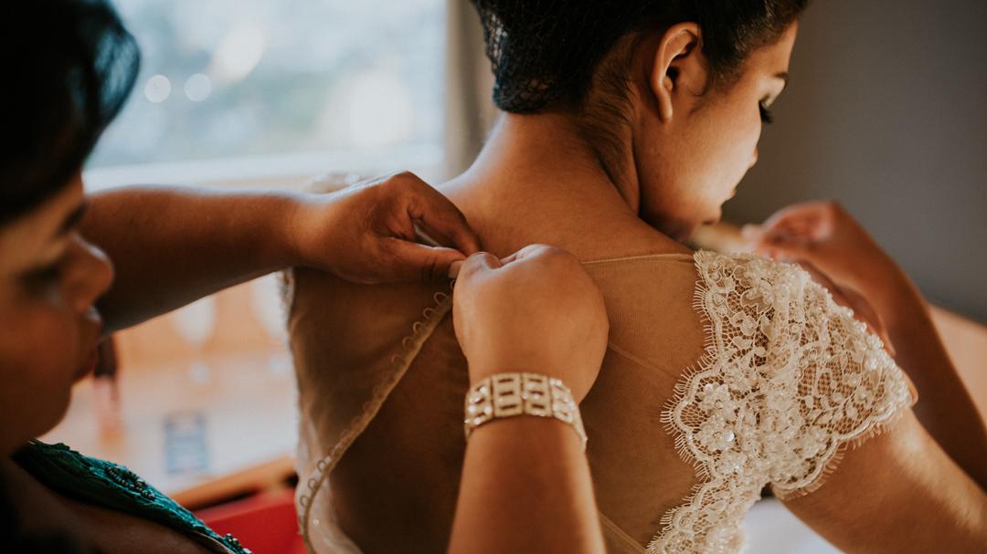 mãe colocando o vestido na noiva