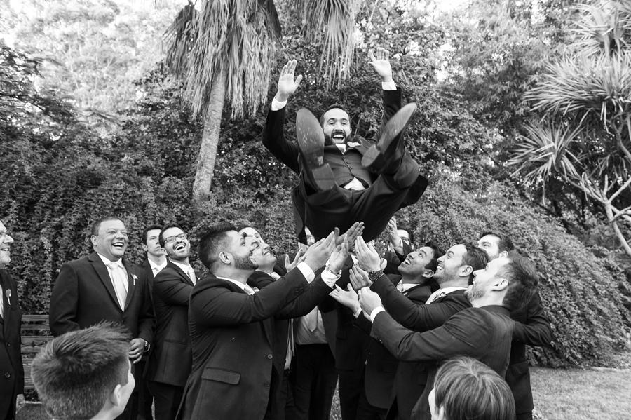 Padrinhos celebram jogando o noivo para cima